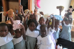 Children at orphanage in Uganda hold up their toys